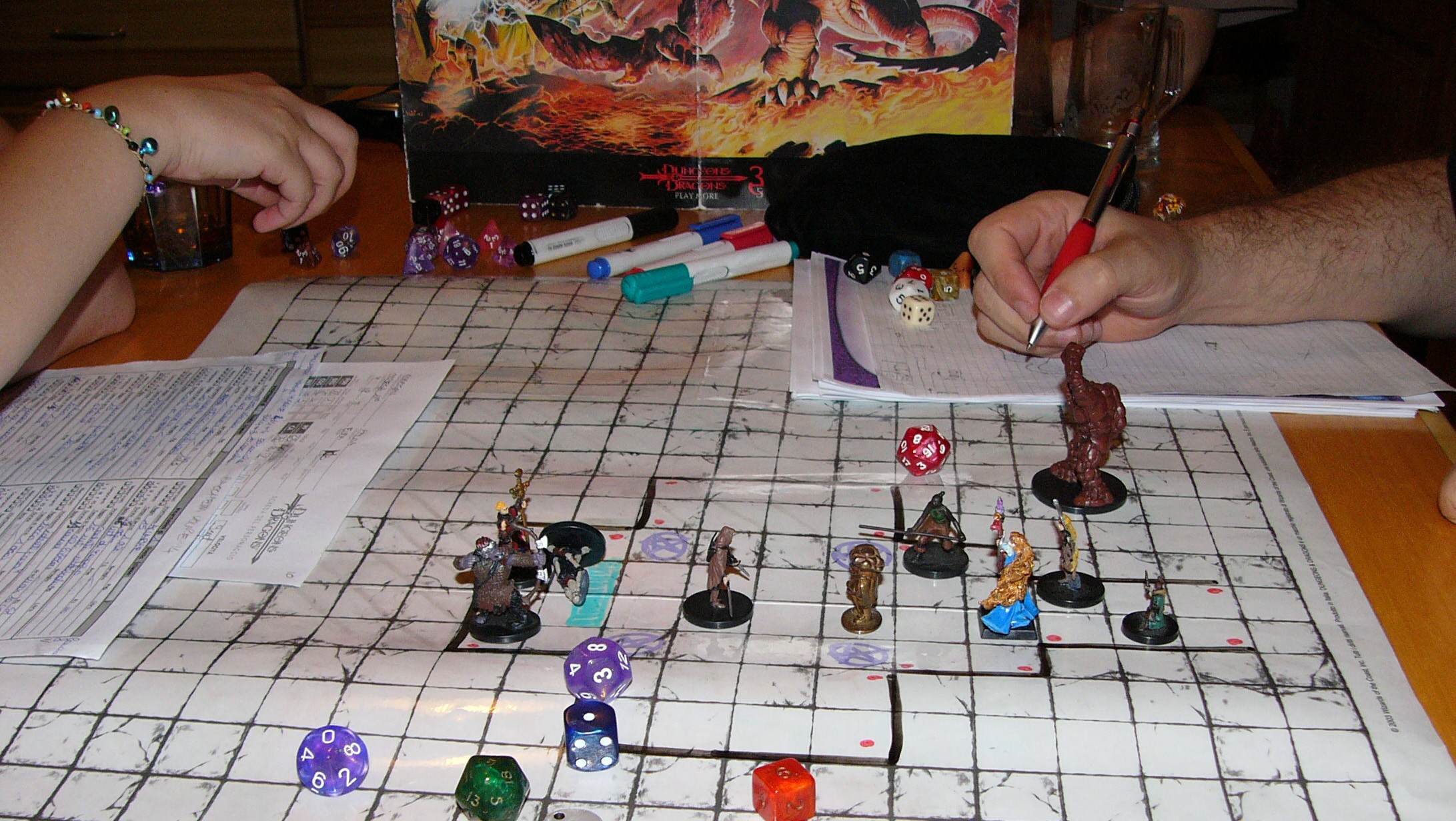 Mid-combat on a battle grid with figures and dice.