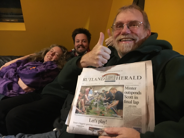 An older man with glasses and a beard gives a thumb's up while holding up a newspaper with a front page article about Carnage, with the headline 'Let's play!'