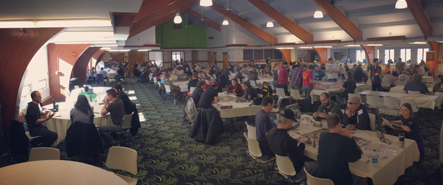 A panoramic view of a ski lodge ballroom full of people playing tabletop games.