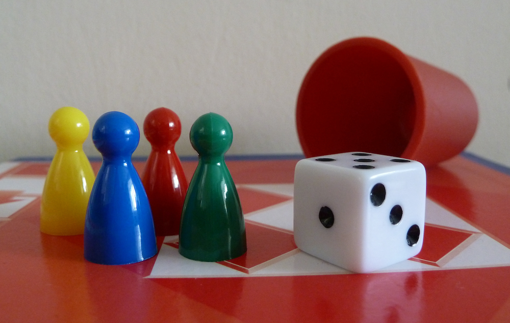 Traditional game pieces: four colored pawns, a six-sided die and a red cup for rolling dice.