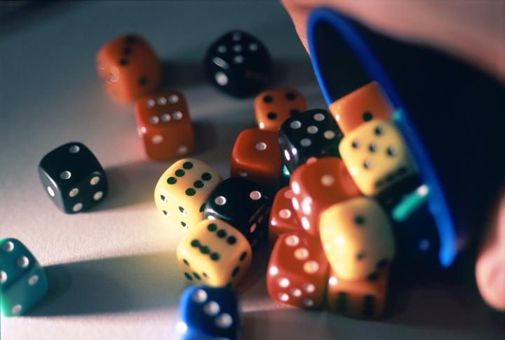 A blue cup spills many multi-colored dice onto the table.